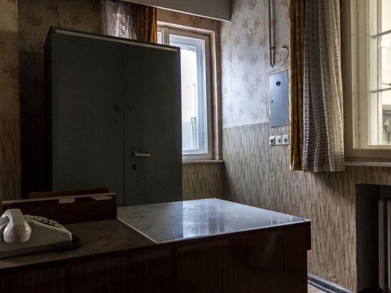 Il primo controllo. Dalla finestra sullo sfondo si può intuire la luce abbagliante con la quale il prigioniero veniva accolto: dopo aver viaggiato al buio e incappucciato per ore veniva esposto alla violenza delle lampade artificiali del garage.